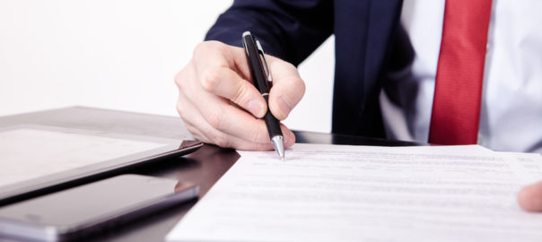 Shoot of financial director's hands signing business contract at the desk in his office